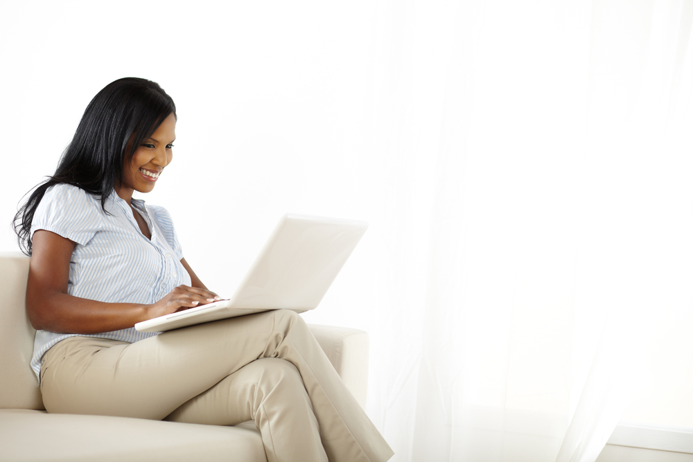 Pretty happy young woman using a laptop